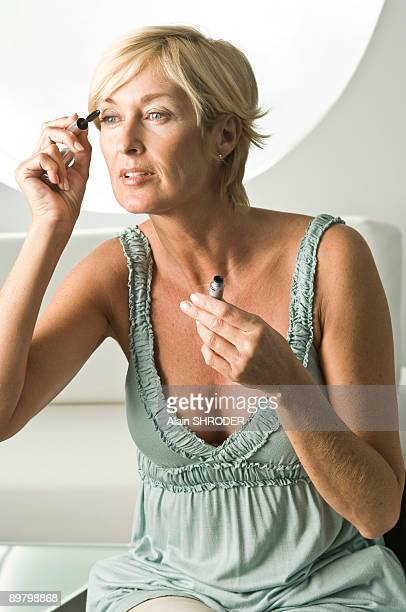close-up of a woman applying mascara on her eyelash - cleavage stock pictures, royalty-free photos & images