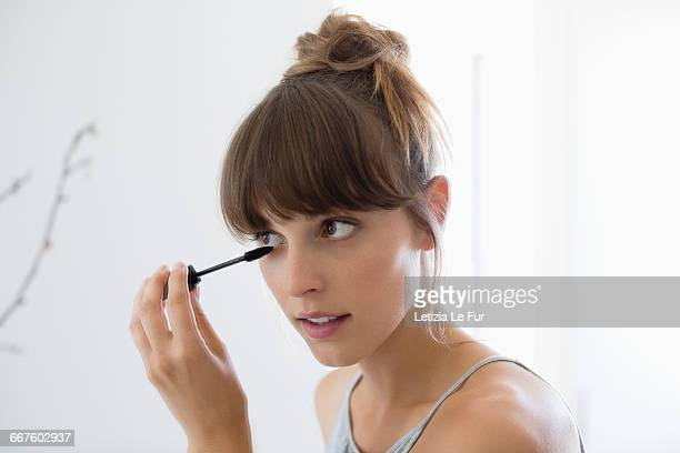 close-up of a woman applying mascara - aplicando - fotografias e filmes do acervo