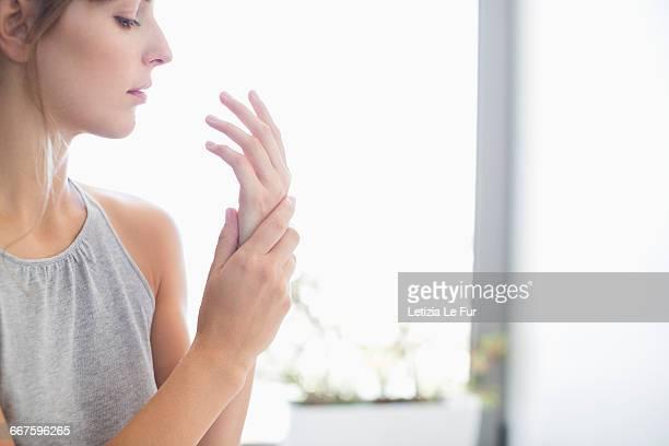 close-up of a woman applying moisturizer on her hands - cuidado del cuerpo fotografías e imágenes de stock