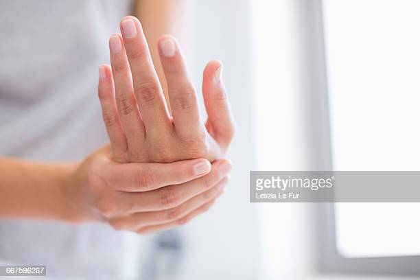 Close-up of a woman applying moisturizer on her hands