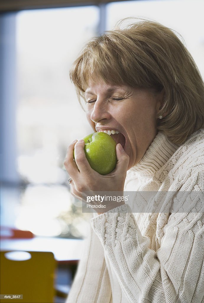 Close-up of a woman biting an apple : Foto de stock