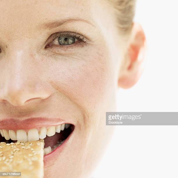 close-up of a woman biting into a cookie