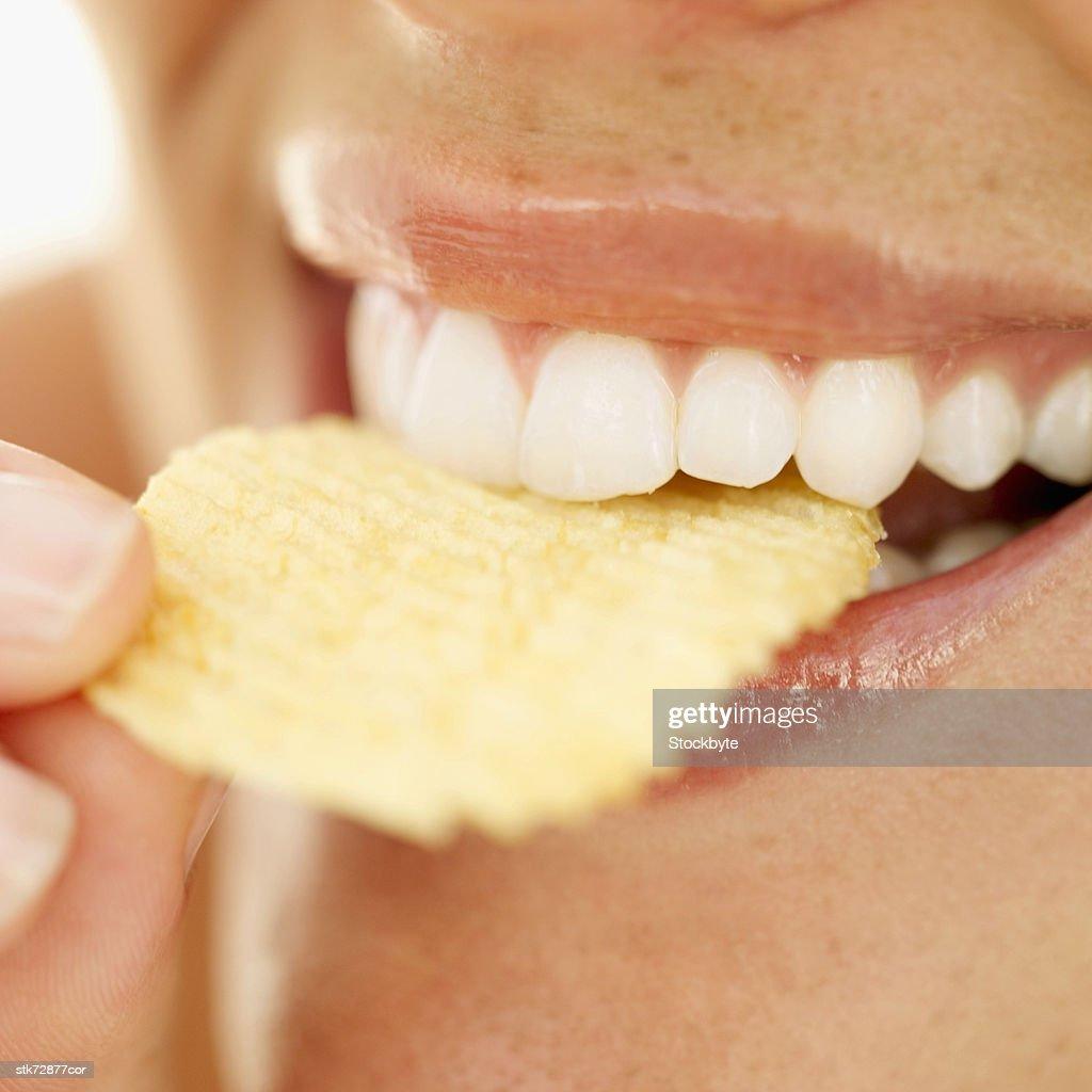 Close-up of a woman biting into a crisp : Stock Photo