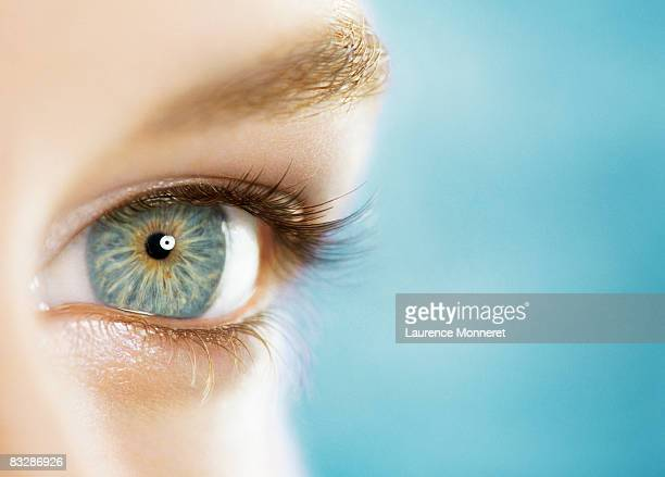 Close-up of a woman blue eye on blue background