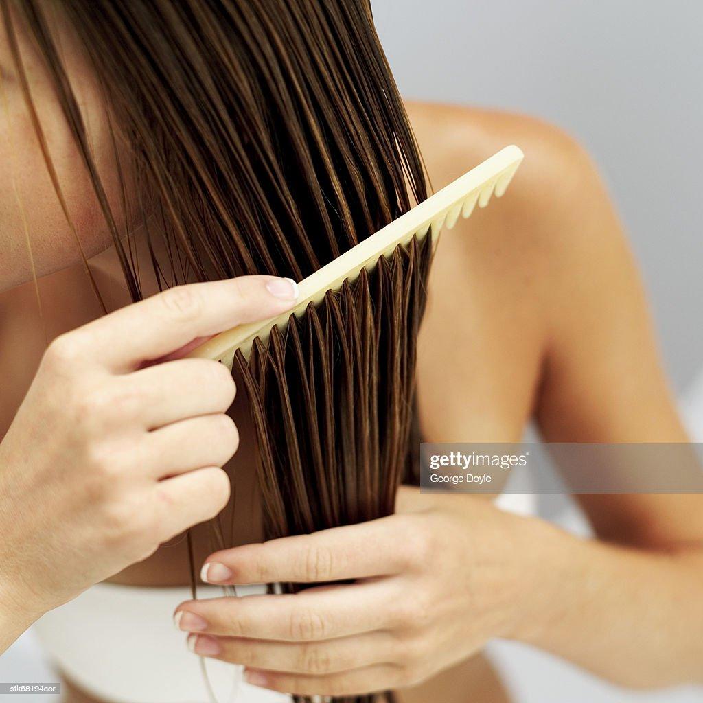 close-up of a woman combing her wet hair : Foto de stock
