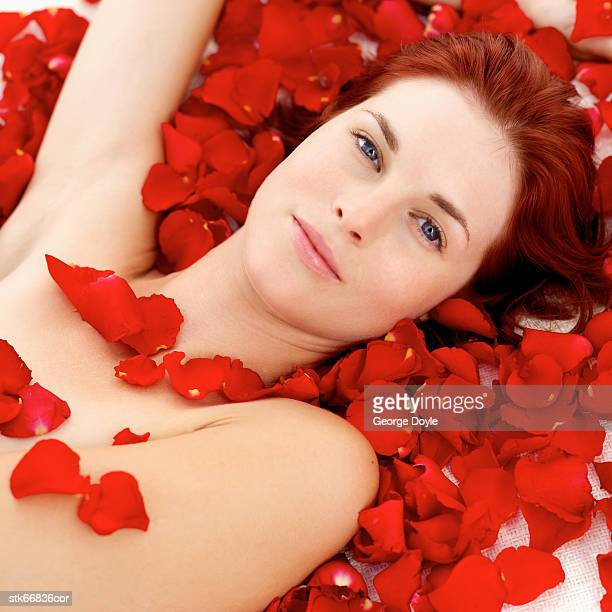 close-up of a woman covered in rose petals