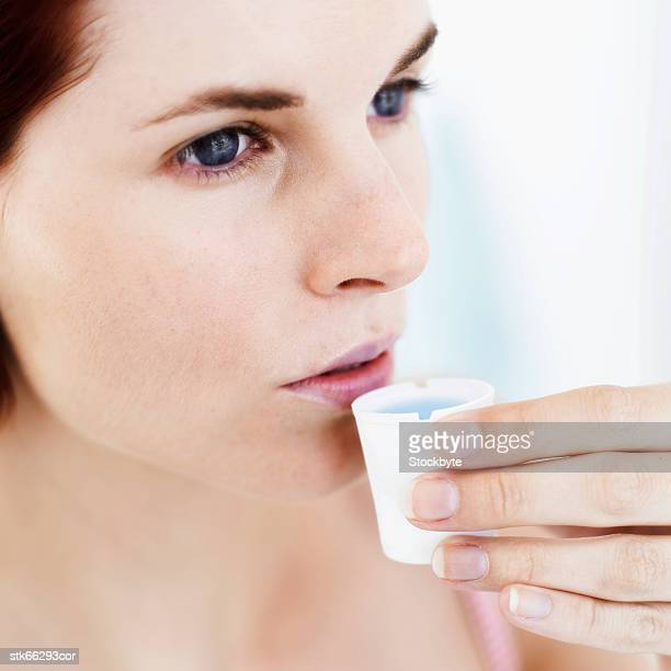 Close-up of a woman drinking medicine from a cup