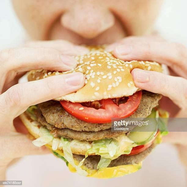 Close-up of a woman eating a hamburger