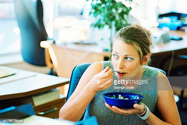close-up of a woman eating soup watchfully