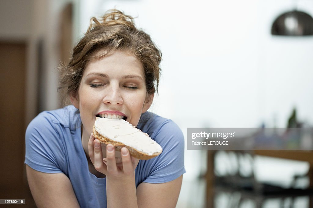 Close-up of a woman eating toast with cream spread on it : Stock Photo