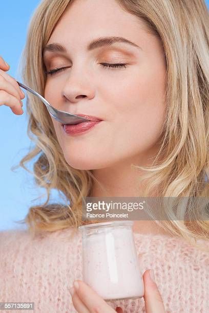 Close-up of a woman eating yogurt