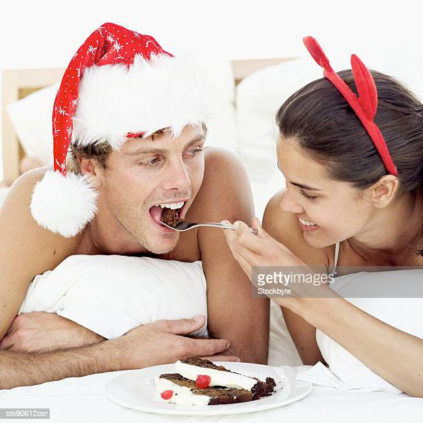 close-up of a woman feeding a man Christmas cake