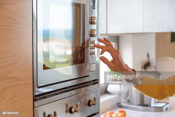 Close-up of a woman hand pushing button of an oven