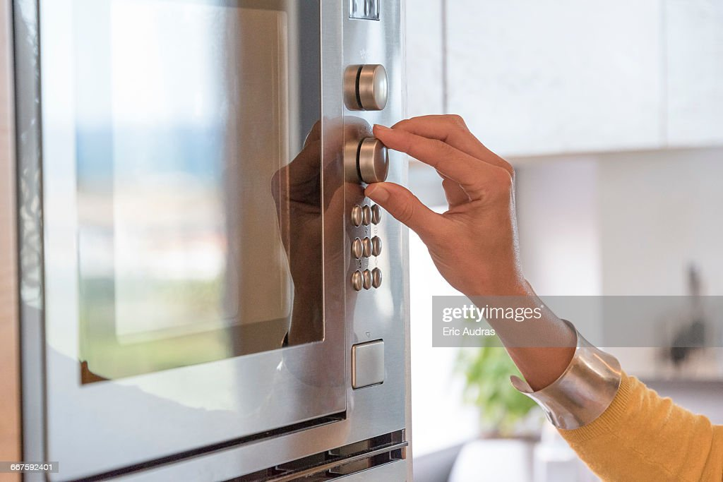 Close-up of a woman hand using an oven : Stock Photo