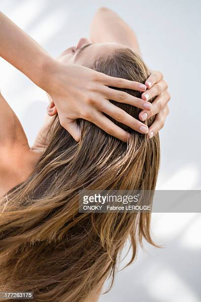 close-up of a woman holding her hair - cheveux ou poils photos et images de collection