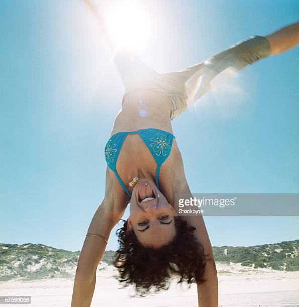 close-up of a woman in a bikini doing a handstand on the beach