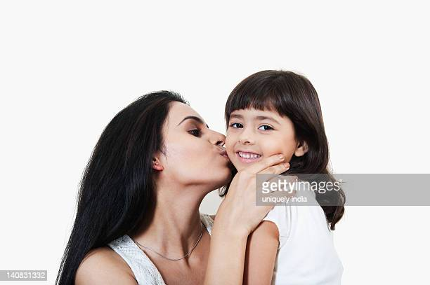 close-up of a woman kissing her daughter - indian girl kissing stock photos and pictures