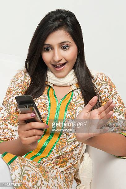 Close-up of a woman looking surprised while reading text message on a mobile phone