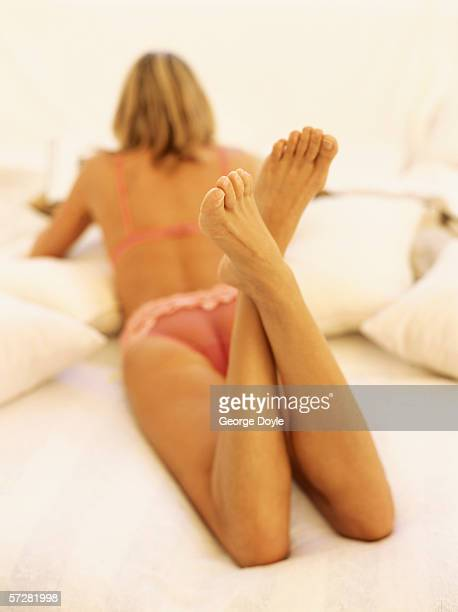 close-up of a woman lying on a bed - woman lying on stomach with feet up stock photos and pictures