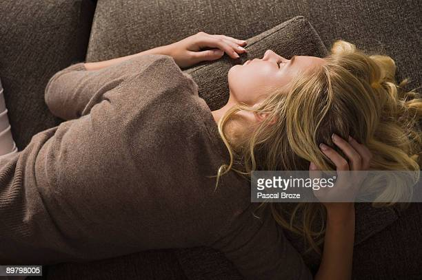 close-up of a woman napping on a couch - lying on front stock pictures, royalty-free photos & images