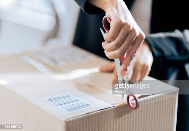 close-up of a woman opening her courier parcel - unboxing stock pictures, royalty-free photos & images