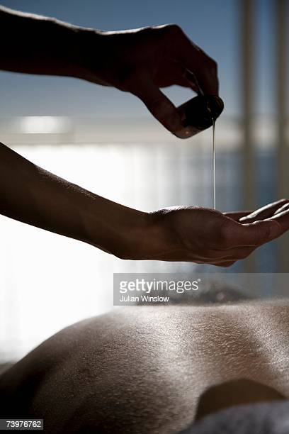 Close-up of a woman pouring oil onto her hands before massaging a man's back