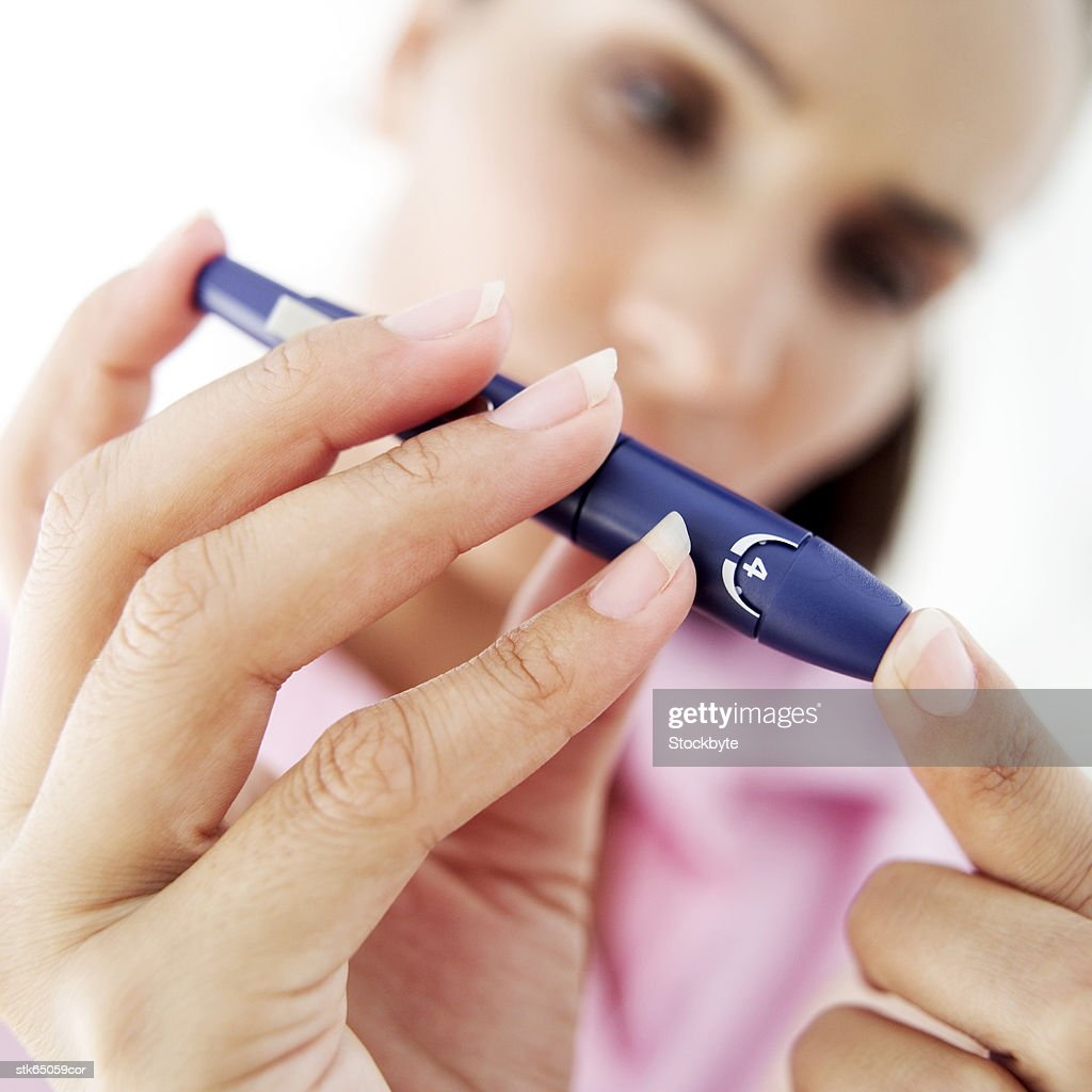 close-up of a woman removing blood from her finger for a blood test : Stock Photo