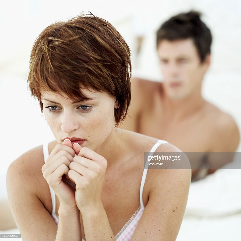 close-up of a woman sitting in a pensive mood with a man behind her : Bildbanksbilder
