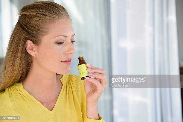 close-up of a woman smelling tea tree oil - aromatherapy stock pictures, royalty-free photos & images