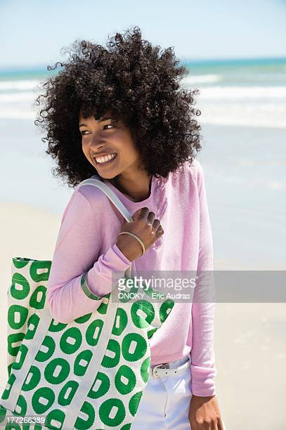 close-up of a woman smiling on the beach - woman carrying tote bag stock photos and pictures