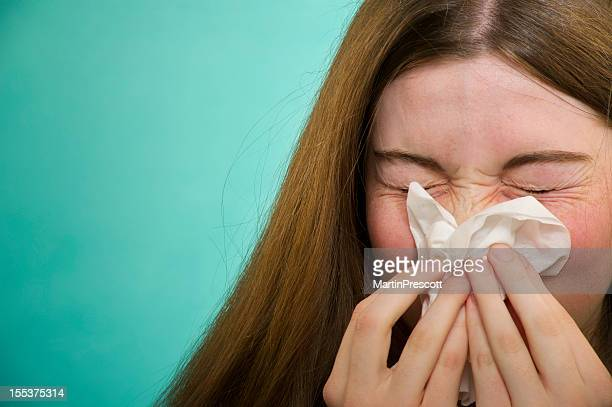 Close-up of a woman sneezing and covering her nose
