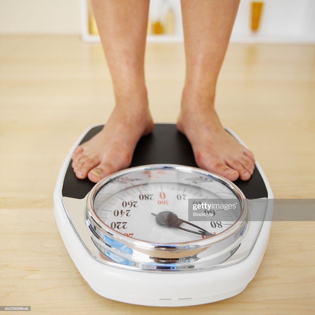 Close-up of a woman standing on a weighing scales : Stock Photo