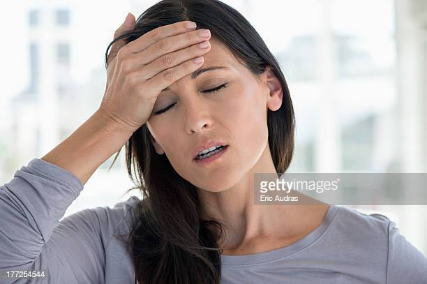 close-up of a woman suffering from a headache - hispanic person sick fotografías e imágenes de stock