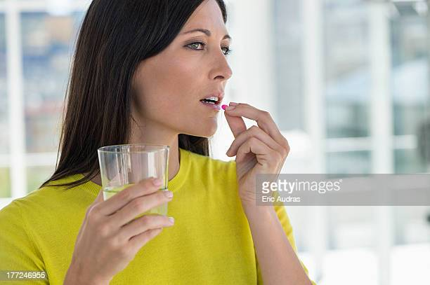 close-up of a woman taking medicine - taking a pill stock pictures, royalty-free photos & images