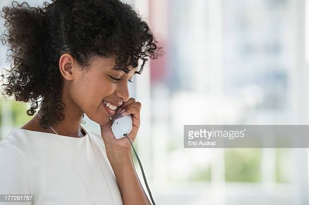 Close-up of a woman talking on a landline phone