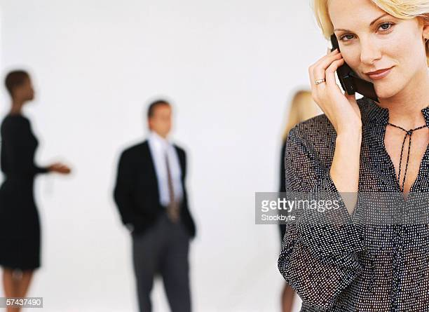 close-up of a woman talking on a mobile phone with people standing behind
