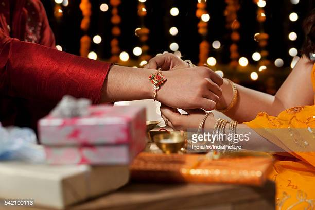 close-up of a woman tying rakhi on her brothers hand - raksha bandhan stock photos and pictures