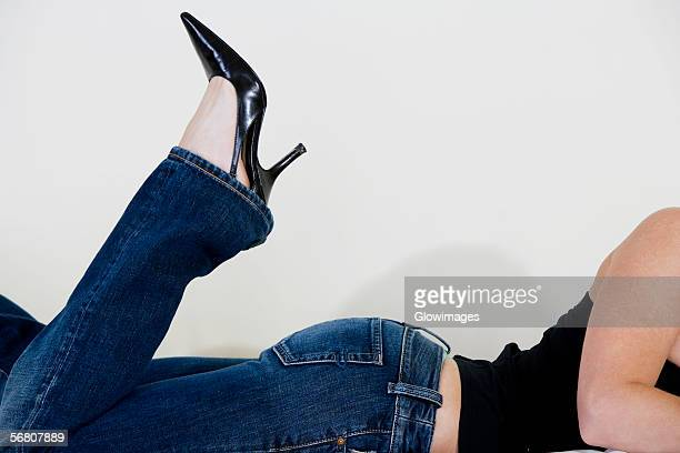 close-up of a woman wearing stilettos - woman lying on stomach with feet up stock photos and pictures