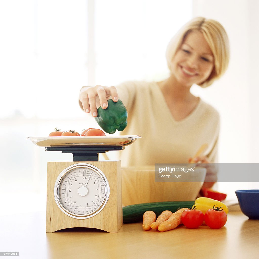close-up of a woman weighing vegetables on a kitchen weighing scale : Stock Photo