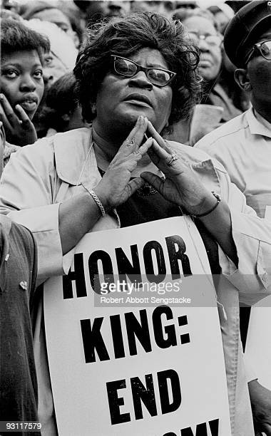 Closeup of a woman who holds a sign that reads in part 'Honor King' a reference to the recently assassinated Civil Rights leader Dr Martin Luther...