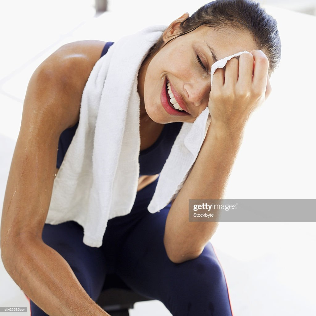 Close-up of a woman wiping her face with a towel : Stock Photo