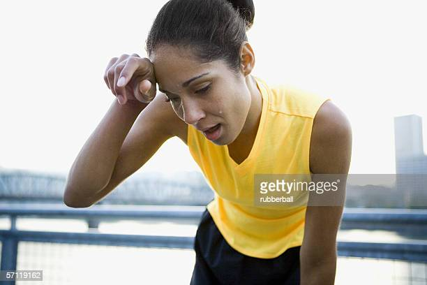 close-up of a woman wiping sweat from her brow - forehead stock pictures, royalty-free photos & images