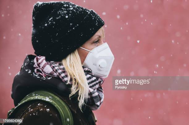 close-up of a woman with a face mask in a snowfall - fingerless gloves stock pictures, royalty-free photos & images
