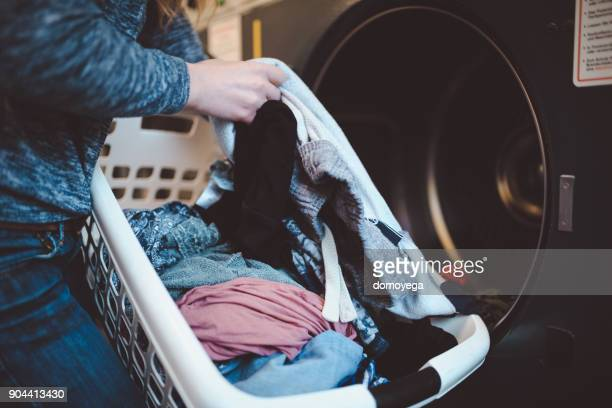 Close-up of a woman with a laundry basket washing clothes