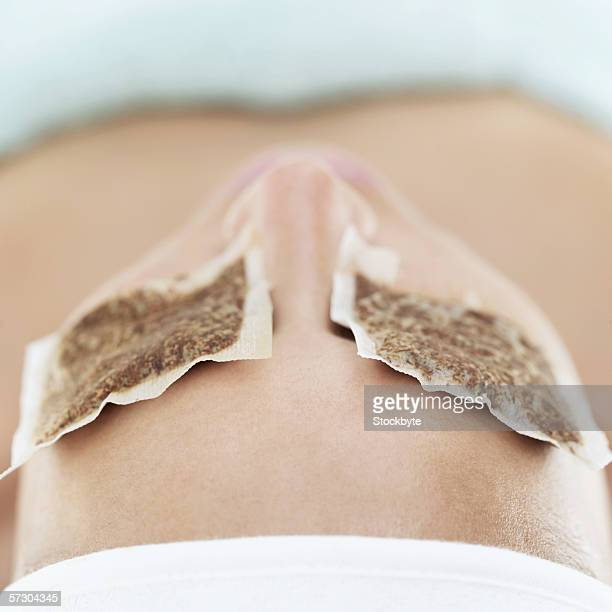Close-up of a woman with teabags on eyes