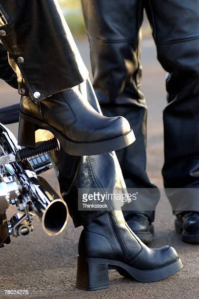 Close-up of a woman's biking boots as she sits on the motorcycle.