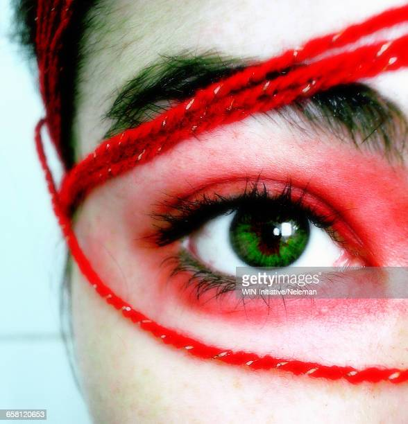 Close-up of a womans eye with red wool around it