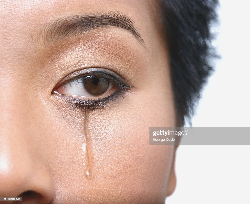 close-up of a woman's eye with tears rolling down : Stock Photo
