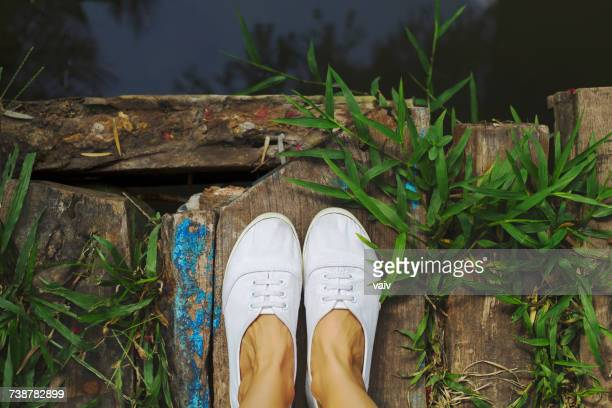 close-up of a womans feet standing on a wooden bridge - white women feet stock pictures, royalty-free photos & images