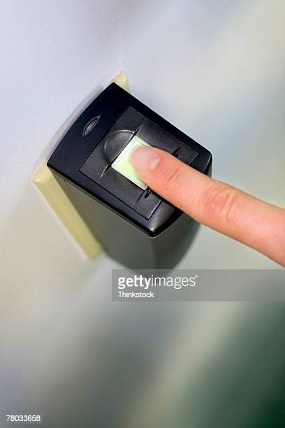 Close-up of a woman's finger on a fingerprint scanner for security system